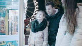 Beautiful family in an amusement park playing at night. The father plays the game wanting to win. stock footage