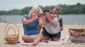 Beautiful family at beach making selfie with phone Stock Images