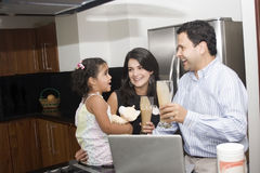 Beautiful family cooking in kitchen. Portrait of beautiful family cooking in kitchen, dad, mom and little daughter royalty free stock photos