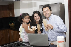 Beautiful family cooking in kitchen. Portrait of beautiful family cooking in kitchen, dad, mom and little daughter stock images