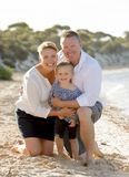 Beautiful family couple wife and husband holding little daughter on beach Royalty Free Stock Image