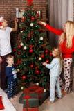 Beautiful family decorates Christmas pine Stock Photos