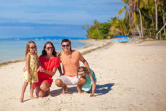 Beautiful family of four have fun on the beach in Stock Image
