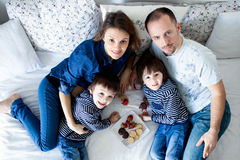 Beautiful family of four, lying on the bed, eating strawberries Royalty Free Stock Images