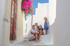Beautiful family of four sitting on doorstep at Royalty Free Stock Image