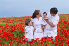 Beautiful family of four standing in a gorgeous po. Beautiful happy family of four standing in a gorgeous poppy flower field Royalty Free Stock Image