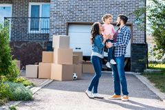 Beautiful family in front of new house with many boxes standing on pathway. To garage stock photos