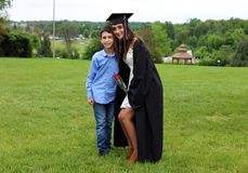Beautiful siblins and girl in black Cap, Gown and Tass, sexy teenager. Unique gorgeous face, nice smile, wonderful eyes girl. Beautiful family in graduation Royalty Free Stock Images