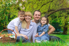 Beautiful family with kids having picnic outdoors. In spring Stock Photos