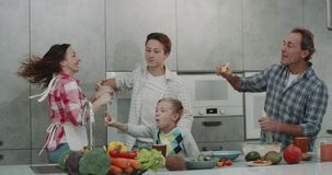 Beautiful family in the kitchen have a great time dacing and making bubbles , adult parents and two boy 9 years old and stock footage