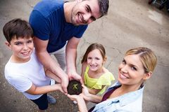 Beautiful family looking at camera while holding a plant in the greenhouse. Portrait of beautiful family looking at camera while holding a plant in the royalty free stock photo