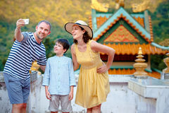 Beautiful family making a self portrait with mobile phone, The Chinese Temple, Koh Phangan island, Thailand. Asia royalty free stock photo