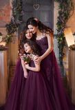 A beautiful family outfit. Mom and two daughters hug each other with love and tenderness in luxurious purple-burgundy. Dresses. Girls have long curly hair. Art Royalty Free Stock Photos