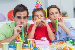 Beautiful family playing with party horns Stock Images