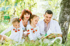 Beautiful family reading book together in park Stock Photography