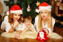 Beautiful family in red Santa hats lying near Christmas tree. Beautiful family of mother and daughter in red Santa hats and a son near Christmas tree lying on Royalty Free Stock Photo