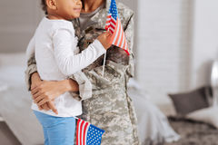Beautiful family sharing their patriotic feelings. Doing it for my county. Stunning passionate attached mother and daughter holding flags in their hands while stock image