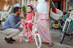 Beautiful family shopping new bicycle for girl. In bike shop stock photo