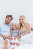 Beautiful family sitting in the bed Stock Photography