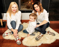 Beautiful family sitting on the fur carpet near fireplace Royalty Free Stock Photos