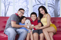Beautiful family sitting on sofa with puppy Stock Photo