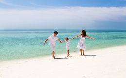 Beautiful family of three dancing on a tropical beach. Beautiful happy family of three dancing on a tropical beach Stock Photo