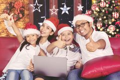 Beautiful family with thumb up at Christmas day Stock Image