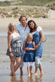 Beautiful family together. Beautiful young family standing together by the water edge on the beach Royalty Free Stock Image