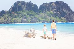 Family on vacation. Beautiful family of two, father and son, walking together at the beach enjoying summer vacation, white sand beach and turquoise lagoon Royalty Free Stock Photo