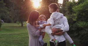 Beautiful family two kids and young parents have a great time together in the middle of the green park in front of the. Camera. 4k stock video footage