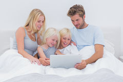 Beautiful family using a laptop in bed Royalty Free Stock Photography