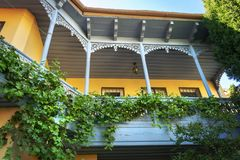 Beautiful and famous colorful Tbilisi wooden balcony with wine grape growing around stock images