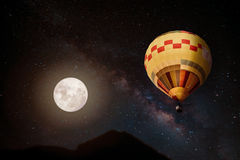 Beautiful fantasy of hot air balloon and full moon with milky way star in night skies background. Stock Images