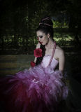 Beautiful fantasy woman in pink sitting in a forest royalty free stock photos