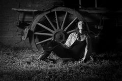 Beautiful farm girl leaning against old wagon. Black and white monochrome image of a beautiful brunette farm girl with hat resting on the ground against a retro Royalty Free Stock Images