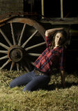 Beautiful farm girl posing in front of old wagon. Black and white monochrome image of a beautiful brunette farm girl with hat resting on the ground against a Stock Photos