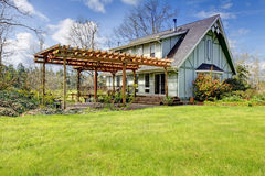 Beautiful farmhouse with attached pergola. Early spring Stock Photo