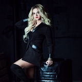 Beautiful fashion blonde woman in black sitting on a metal barrel. Totally dark style Royalty Free Stock Images