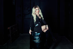 Beautiful fashion blonde woman in black sitting on a metal barrel. Totally dark style. Beautiful fashion blonde woman in black sitting on a metal barrel Stock Photos