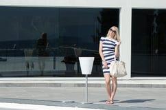 Beautiful fashion blonde woman presenting a white handbag Royalty Free Stock Images