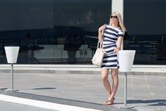 Beautiful fashion blonde woman presenting a white handbag Stock Photography