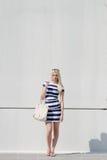 Beautiful fashion blonde woman presenting a white handbag Stock Image