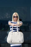 Beautiful fashion blonde woman presenting a white handbag. Leaning on a dark glass partition Royalty Free Stock Photography