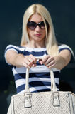Beautiful fashion blonde woman presenting a white handbag. Leaning on a dark glass partition Royalty Free Stock Images