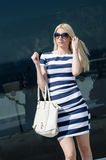 Beautiful fashion blonde woman presenting a white handbag. Leaning on a dark glass partition Stock Photos