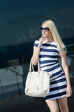 Beautiful fashion blonde woman presenting a white handbag. Leaning on a dark glass partition Royalty Free Stock Photos