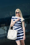 Beautiful fashion blonde woman presenting a white handbag. Leaning on a dark glass partition Stock Photo