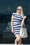 Beautiful fashion blonde woman presenting a white handbag Stock Photos