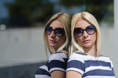 Beautiful fashion blonde woman wear sunglasses. Leaning on a dark glass partition Royalty Free Stock Image