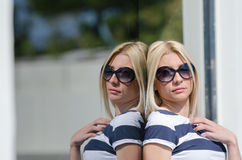 Beautiful fashion blonde woman wear sunglasses. Leaning on a dark glass partition Royalty Free Stock Images
